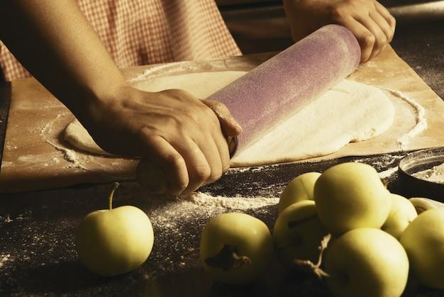 女性は秋のアップルパイを準備します