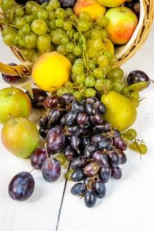 白い木製のテーブルの上の秋の果物と大きなバスケット