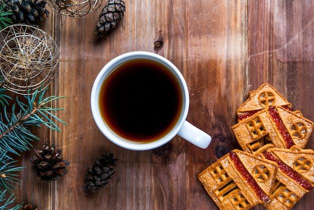 Чашка чая и печенье на деревянном столе. возле елки ветка, шишки и елочные шары.