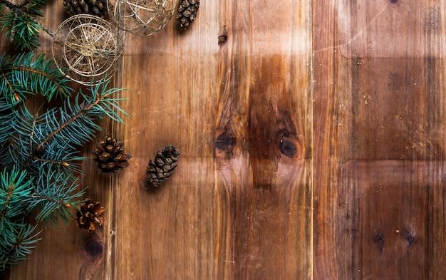 クリスマスツリー、クリスマスボール、コーンの枝とクリスマスの木製の背景