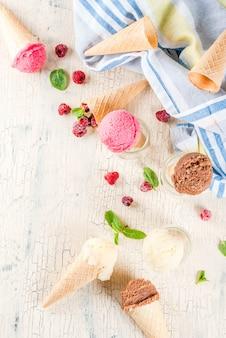 Летние сладкие ягоды и десерты, с разнообразным вкусом мороженого в шишках розового (малинового), ванильного и шоколадного с мятой на светлом бетоне