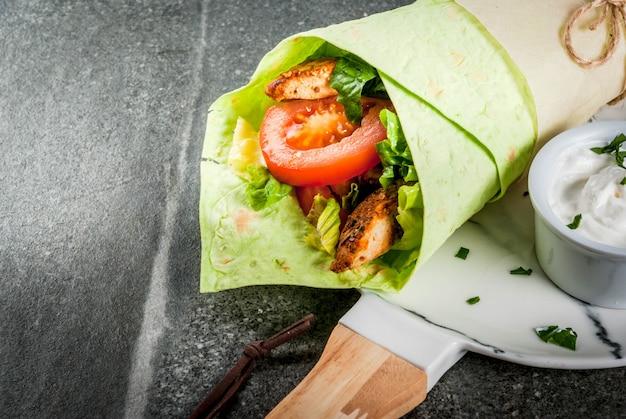 緑のトルティーヤでサンドイッチを包む