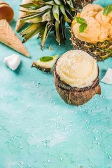 夏の休日の休暇の概念、さまざまなトロピカルアイスクリームシャーベット、パイナップル、グレープフルーツ、ココナッツ、ライトブルーコンクリートの冷凍ジュースを設定