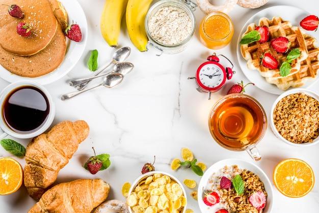 健康的な朝食を食べる概念、様々な朝の食べ物-パンケーキ、ワッフル、クロワッサンオートミールサンドイッチ、グラノーラとヨーグルト、フルーツ、ベリー、コーヒー、紅茶、オレンジジュース、白い背景