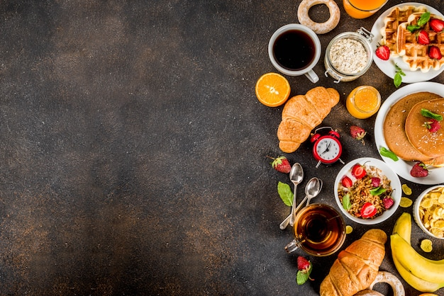 健康的な朝食のコンセプト、様々な朝の食べ物-パンケーキ、ワッフル、クロワッサンオートミールサンドイッチ、グラノーラとヨーグルト、フルーツ、ベリー、コーヒー、紅茶、オレンジジュースの背景