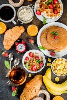 Концепция здорового завтрака, разнообразная утренняя еда - блины, вафли, сэндвич с овсяной кашей и мюсли с йогуртом, фруктами, ягодами, кофе, чаем, апельсиновым соком