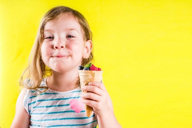 Летняя веселая концепция праздника, милая белокурая девушка малыша ест ягоды из вафельного рожка мороженого, ярко-желтый фон