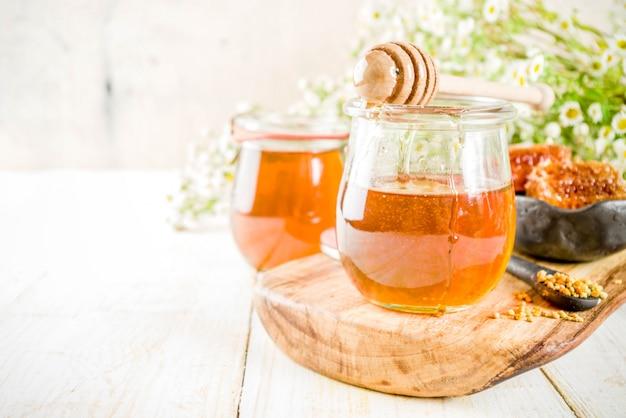 オーガニックの花の蜂蜜、瓶、花粉と蜂蜜の櫛、白い木製のテーブル、野生の花