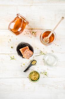 オーガニックの花の蜂蜜、瓶、花粉と蜂蜜の櫛、白い木製のテーブルの上、野生の花のトップビュー