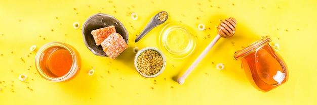 オーガニックの花の蜂蜜、瓶、花粉と蜂蜜の櫛、野生の花の創造的なレイアウト明るい黄色の壁トップビューコピースペースバナー形式