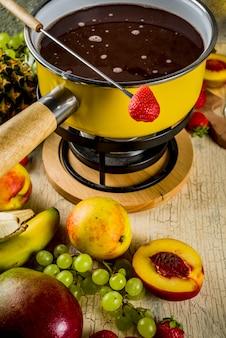 伝統的なフォンデュポットにチョコレートフォンデュ、フォーク、白ワイン、各種ベリーとフルーツの盛り合わせ