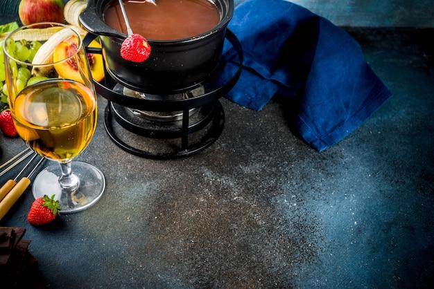 伝統的なフォンデュポットにチョコレートフォンデュ、フォーク、白ワイン、各種ベリーとフルーツの盛り合わせ、コピースペース