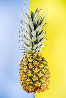 明るい青黄色の壁コピースペースに新鮮な丸ごとパイナップル