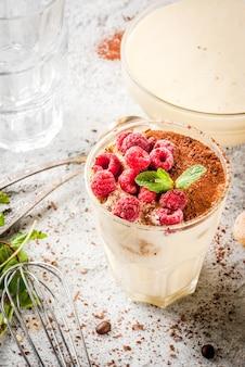 Приготовление итальянской еды на десерт тирамису, со всеми необходимыми ингредиентами какао, кофе, сыром маскарпоне, мятой и малиной