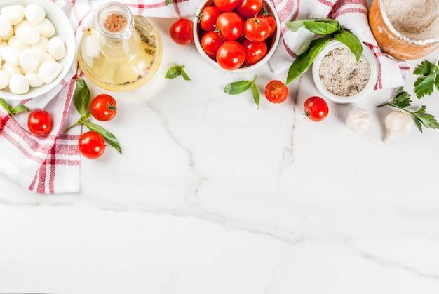 小麦粉、オリーブオイル、バジル、トマト、キッチンアクセサリートップビューで白い大理石のテーブルに自家製パスタピザイタリア料理の食材