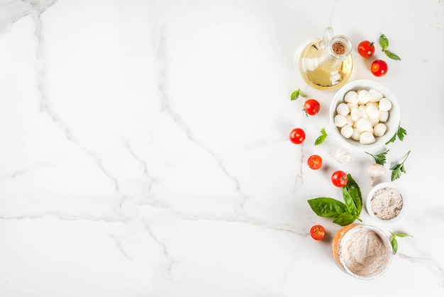 Домашняя паста пицца итальянский пищевой ингредиент на белом мраморном столе с видом сверху муки, оливкового масла, базилика, помидоров и кухонных принадлежностей