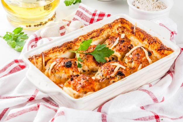 自家製の健康的な食事の夕食、ソース、チーズ、野菜入りの七面鳥のミートボールを用意しました。スパイスの入った白い大理石のテーブルの上。