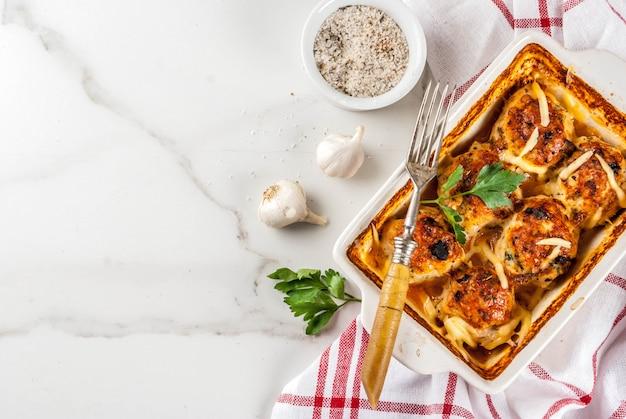 Домашний здоровый диетический ужин, приготовленные куриные котлеты из индейки с соусом, сыром, зеленью. на белом мраморном столе, со специями.