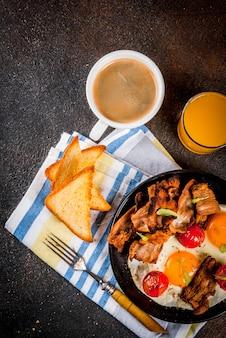 伝統的な自家製イングリッシュアメリカンの朝食、卵焼き、トースト、ベーコン、コーヒーマグカップとオレンジジュース