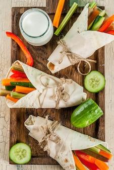 夏のヘルシーなスナック前菜、メキシコ風のトルティーヤサンドイッチラップカラフルな新鮮な野菜スティック(セロリ、ルバーブ、コショウ、キュウリ、ニンジン)をヨーグルトソースで浸した