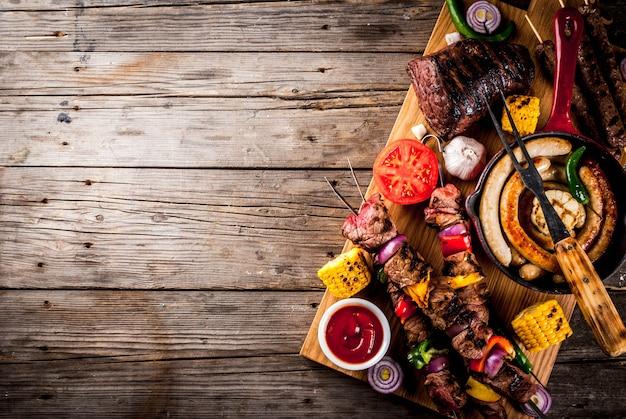 各種バーベキューフードグリル肉、バーベキューパーティーフェスト-シシカバブ、ソーセージ、肉の切り身、新鮮な野菜、ソース、スパイス、古い木製の素朴なテーブル