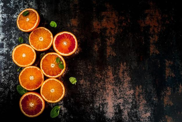 Свежие сырые апельсины крови, половинки, с мятой, на темном ржавом настольном представлении