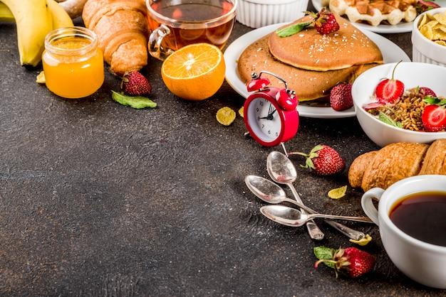 Концепция здорового завтрака, разнообразная утренняя еда - блины, вафли, сэндвич с овсяной кашей и мюсли с йогуртом, фруктами, ягодами, кофе, чаем, апельсиновым соком, темным ржавым столом