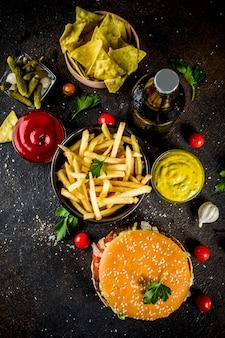 Разнообразная еда для вечеринок, гамбургеры, картофель фри, картофельные чипсы, маринованные огурцы, лук, помидоры и холодные пивные бутылки, ржавый черный бетонный стол