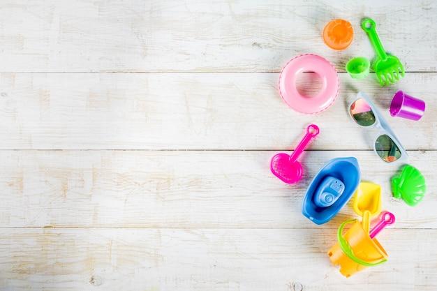 Концепция летних каникул с пластиковыми пляжными детскими игрушками - ведро, совок, грабли, плесень лодка, спасательный круг игрушки белый деревянный стол