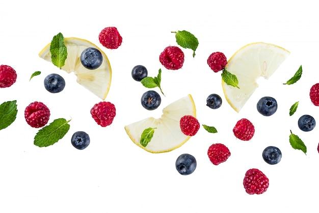 創造的なレイアウト、テーブル、新鮮な果実、白いテーブルにシンプルなパターン。ラズベリー、ブルーベリー、ミントの葉、レモンのスライス。