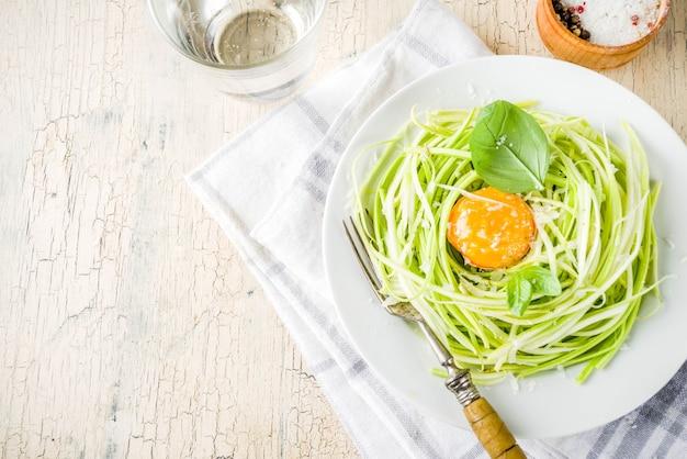 Модные веганские кулинарные рецепты, макароны из спагетти с цуккини, сыром, яичным желтком, пармезаном, оливковым маслом и листьями базилика, легкий бетонный стол