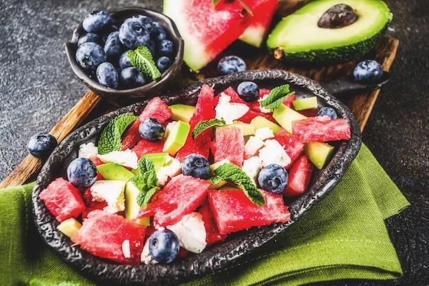 Концепция летней еды, салат из свежего холодного арбуза с сыром фета, черникой, авокадо и мятой
