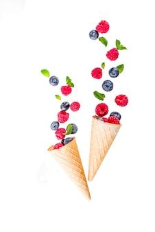 ラズベリーとブルーベリーとワッフルアイスクリームコーン、上記の単純なパターンを持つ創造的なレイアウト