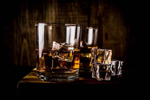 Две рюмки для виски на темном деревянном столе, с кубиками льда,