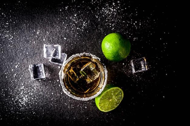 Две рюмки текилы на темном столе, с кубиками льда, солью и лаймами