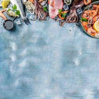 Свежие сырые морепродукты кальмары креветки устричные мидии рыба со специями травы лимона на голубом столе вид сверху