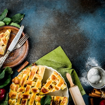 伝統的な秋のベーキング、シナモンと自家製アップルパイ、ローリングロール、シュガーパウダー、新鮮なリンゴ、スパイス、トップビューでダークブルーのテーブル