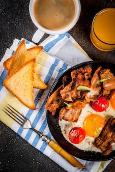 伝統的な自家製イングリッシュアメリカンの朝食、目玉焼き、トースト、ベーコン、コーヒーマグカップ