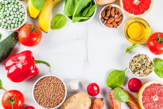 健康食品の背景、トレンディなアルカリダイエット製品-果物、野菜、穀物、ナッツ。オイル、白い大理石の背景トップビューコピースペースフレーム