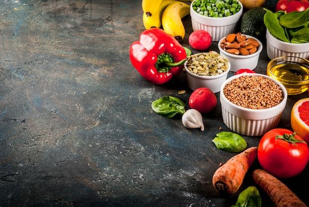 健康食品の背景、トレンディなアルカリダイエット製品-果物、野菜、穀物、ナッツ。油、暗い青色のコンクリート背景コピースペース