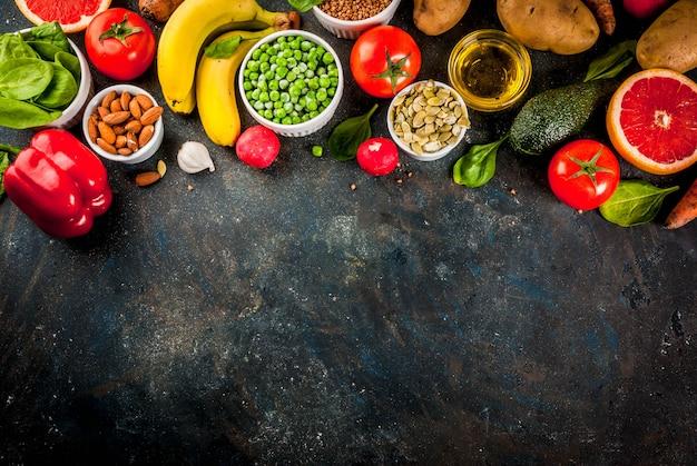 健康食品の背景、トレンディなアルカリダイエット製品-果物、野菜、穀物、ナッツ。油、暗い青色のコンクリート背景平面図