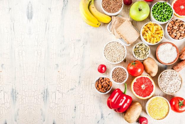 ダイエット食品の背景概念、健康的な炭水化物(炭水化物)製品-果物、野菜、穀物、ナッツ、豆、コピースペース上の光のコンクリート背景