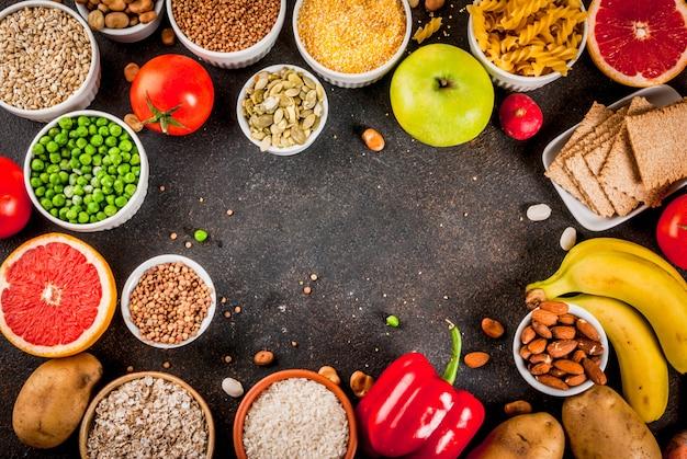 ダイエット食品の背景概念、健康的な炭水化物(炭水化物)製品-果物、野菜、穀物、ナッツ、豆、暗い青色のコンクリート背景コピースペースフレーム