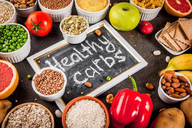 ダイエット食品の背景概念、健康的な炭水化物(炭水化物)製品-果物、野菜、穀物、ナッツ、豆、暗い青色のコンクリート背景