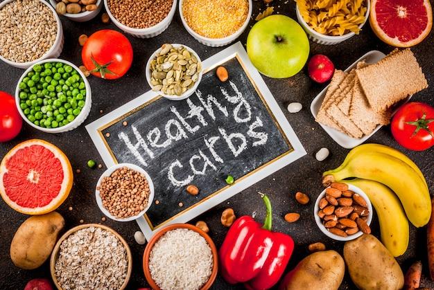 ダイエット食品の背景概念、健康的な炭水化物(炭水化物)製品-果物、野菜、穀物、ナッツ、豆、暗い青色のコンクリート背景トップビュー