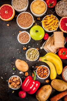 ダイエット食品の背景概念、健康的な炭水化物(炭水化物)製品-果物、野菜、穀物、ナッツ、豆、暗い青色のコンクリート背景平面図コピースペース