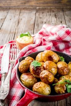 フライパン全体の若いジャガイモ、自家製のベジタリアン料理、木製の古い素朴なテーブル、ソース、コピースペースで焼いた