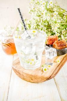 オーガニックダイエットデトックス夏の飲み物、カモミールと蜂蜜、白い木製のテーブル、カモミールの花と瓶の中の蜂蜜と注入水飲料。コピースペース