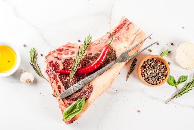 生の牛肉の霜降り肉ストリップロンリブアイステーキとスパイス