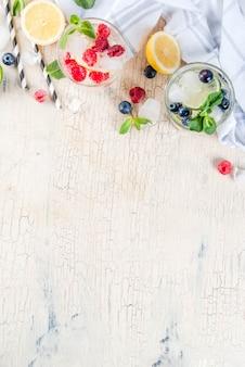 さまざまなベリーレモネードまたはモヒートカクテル、新鮮なアイスレモンライムラズベリーブルーベリー注入水